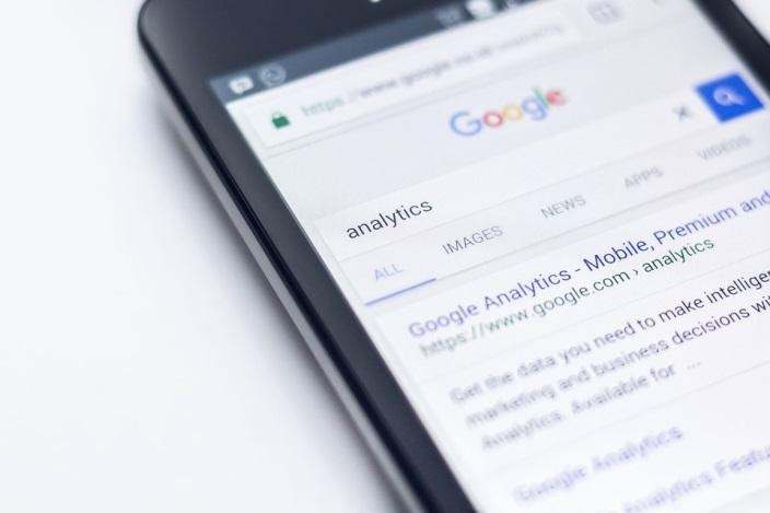 """A black smartphone displaying an """"analytics"""" search query on Google's search engine page."""